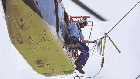 Fast frei über dem Boden sitzt der Monteur am Helikopter, um die schwarzweißen Fähnchen am sogenannten Blitzseil der 110-KV-Leitungen anzubringen. J Foto: EVO